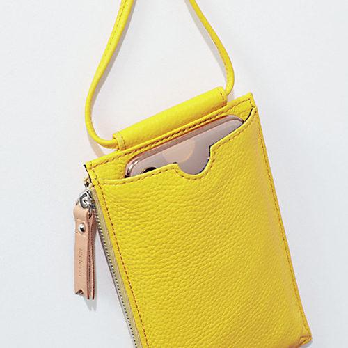 表面のスマホポケットは、 開口部の中央にくぼみをつけて取り出しやすく(写真は iPhone XSを収納)。